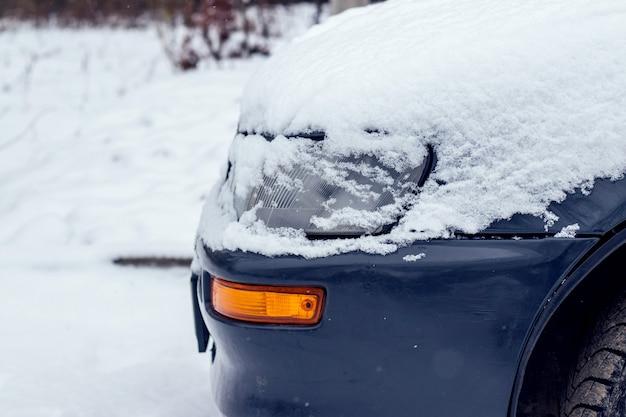 雪の中の車。雪に覆われた車のボンネット。冬の降雪による悪天候