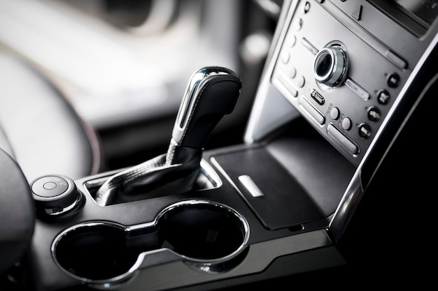 Car inside, automatic transmission close up, cup holders and armrest, black leather seats