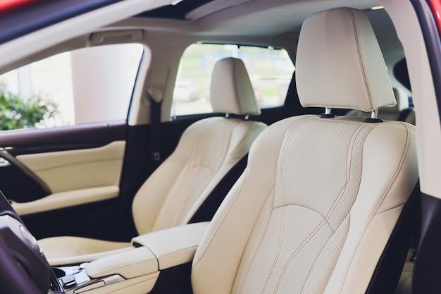 ドライバーの場所内の車。威信の現代車のインテリア。ハンドルダッシュボード付きのフロントシート。孤立した白い背景の上の金属装飾パノラマ屋根とベージュのコックピット。