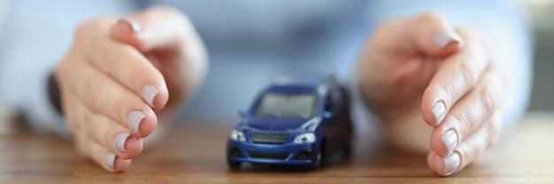 女性の手の中に車。交通事故保険のコンセプト
