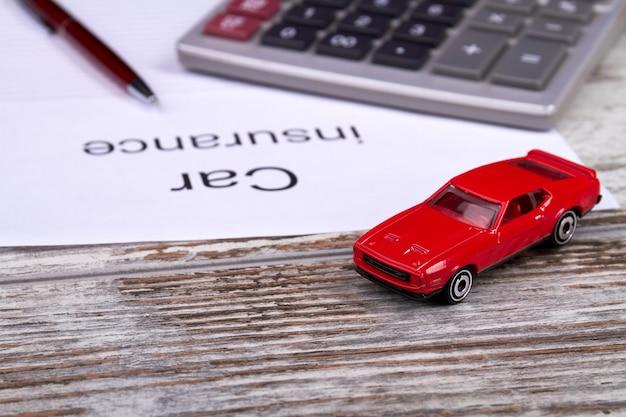 おもちゃの車と電卓の自動車保険会計の概念