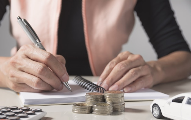 Car insurance and car service. businesswoman with stack of coins and toy car, business