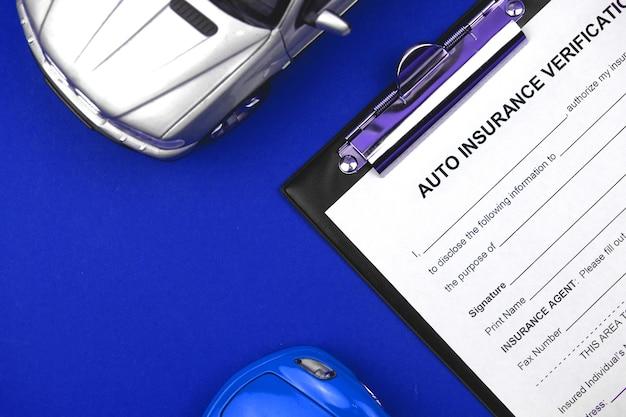 테이블과 사무실 데스크탑에 자동차 장난감이 있는 자동차 보험 청구 양식. 사고 개념으로부터 보호. 상위 뷰 사진