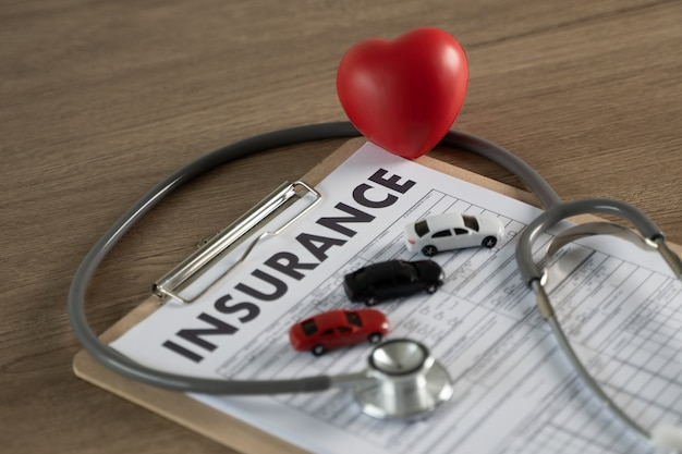 Car insurance in clipboard, stethoscope and heart
