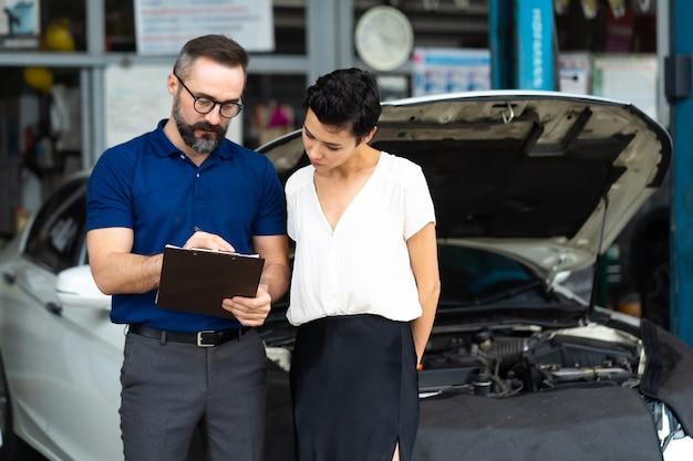 자동차 보험 개념입니다. 보험 대리인은 여성 고객과 함께 손상된 자동차를 검사하여 보고서 청구 양식에 정보를 작성합니다.