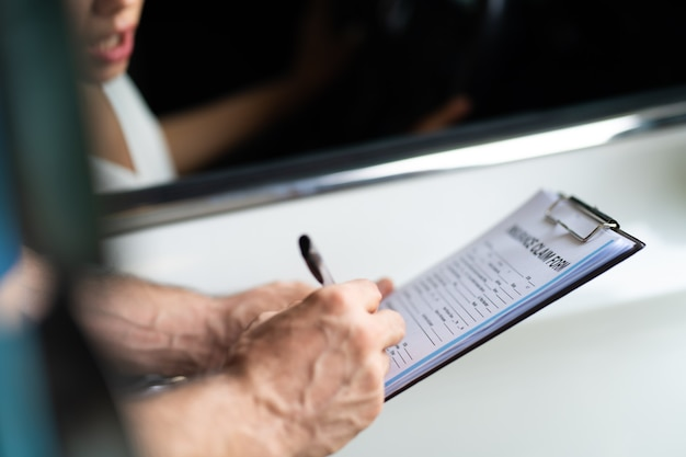 Концепция страхования автомобилей. страховой агент осматривает поврежденный автомобиль вместе с клиенткой-женщиной, записывая информацию в форму заявления о претензии.