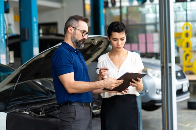 Car insurance concept. insurance agent examine damaged car with woman customer write information on report claim form.