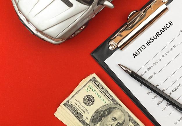 자동차 보험 양식입니다. 에이전트의 사무실 비즈니스 데스크탑에 계약 및 정책, 돈 및 자동차 장난감이 있는 클립보드. 빨간색 배경 및 평면도 사진