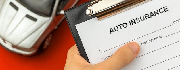 손에 자동차 보험 양식입니다. 배경에 자동차 장난감이 있는 데스크탑. 배너 사진
