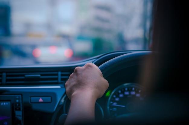 Интерьер автомобиля и рулевое колесо, за рулем своего автомобиля по дороге, фокус на руке, концепция автомобиля и путешествия.