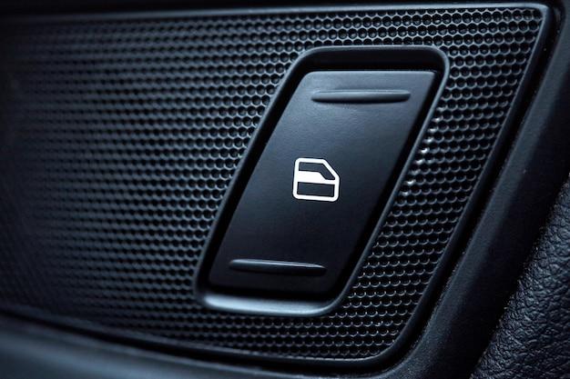 Car interior details of door handle with windows controls and adjustments
