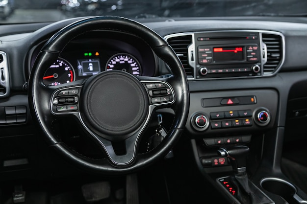 Car interior - steering wheel, shift lever and dashboard, climate control, speedometer, display.