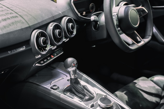 Car interior at transmission shift gear area. modern car interior, gearstick radio and cup
