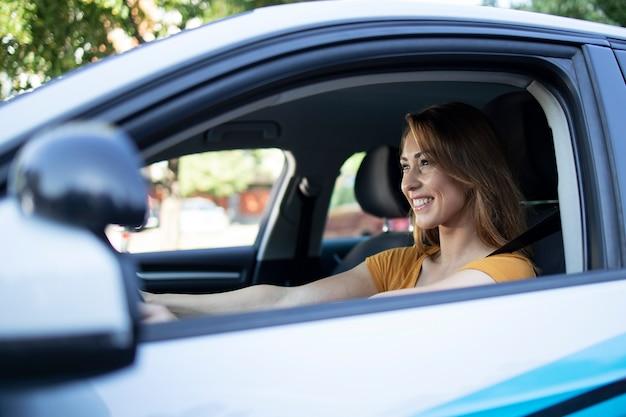 女性ドライバーの車内の眺めは車を運転することを楽しんでいます