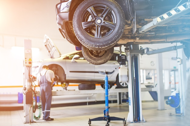 The car is lifted for repair in a car service station