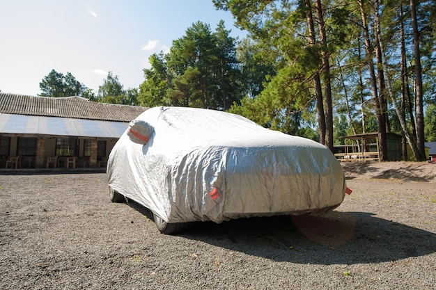 The car is in the parking with auto cover from the sun. protection from heating the car.