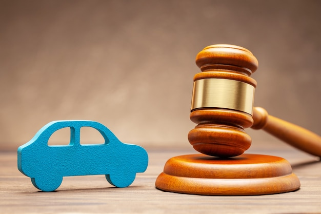Car and judge gavel on brown surface. concept of selling a car by auction or accident sentence.