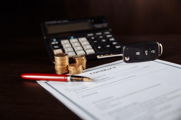 자동차 키와 나무 테이블에 자동차 구매 계약에 동전.