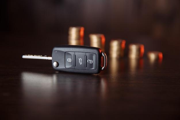 木製の背景に車のキーとコイン、自動車金融業界のコンセプト写真。