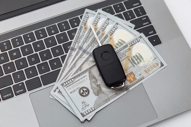ラップトップ上の車のキーとお金。オンライン購入車のコンセプト