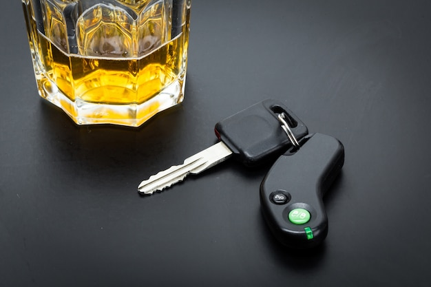 Car key on the bar with spilled alcohol
