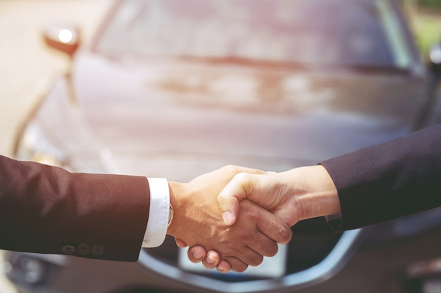 車の鍵、交換を渡すビジネスマンはショールームで他の男に与えます。