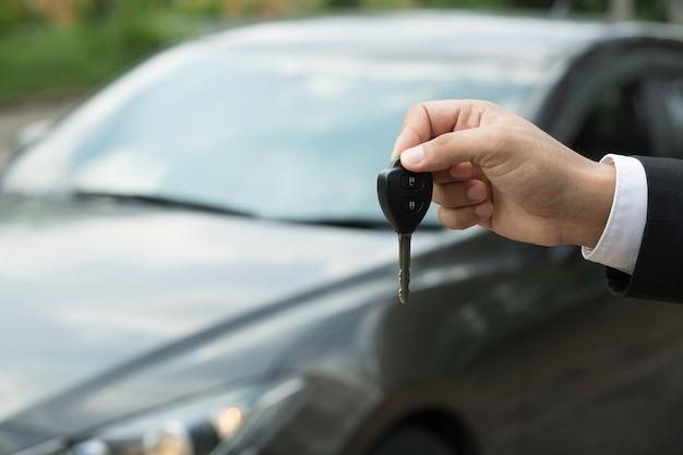 車の鍵、ビジネスマンが車の中で他の人に車の鍵を渡す