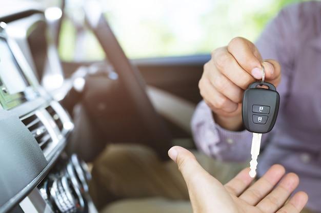자동차 키, 넘겨 사업가 쇼룸에서 자동차 배경에 다른 여자에게 자동차 키를 제공합니다.