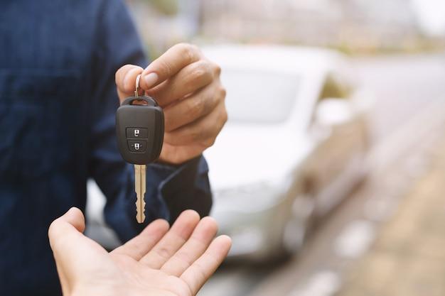 자동차 키, 넘겨 사업가 자동차 배경에 다른 여자에게 자동차 키를 제공합니다.