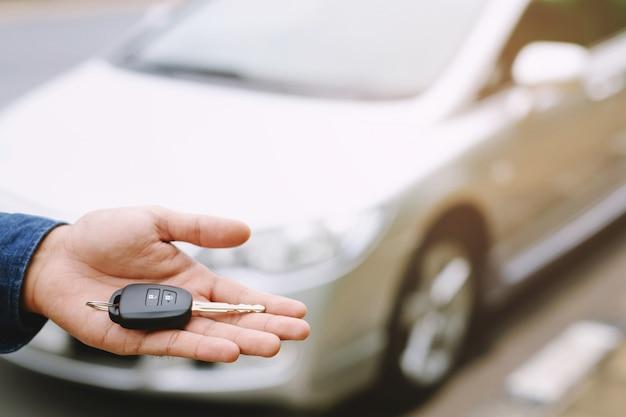 車の鍵、ビジネスマンの引き渡しは、車の背景にある他の女性に車の鍵を渡します。