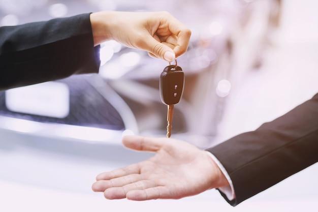 자동차 키, 넘겨 사업가 쇼룸 배경에 다른 여자에게 자동차 키를 제공합니다.