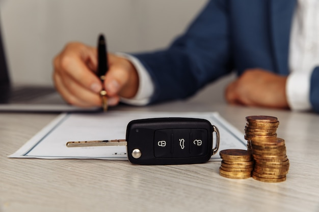 Car key and coins on a contract
