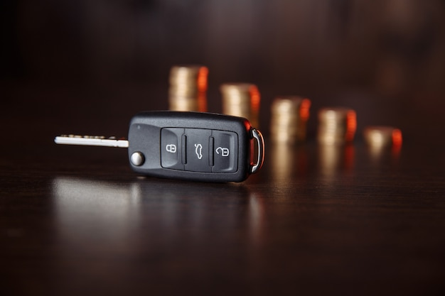 Car key and coins on wooden background, concept photo for car finance industry.