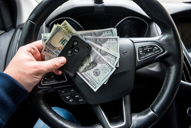 Car key and dollar in hand inside auto. finance concept