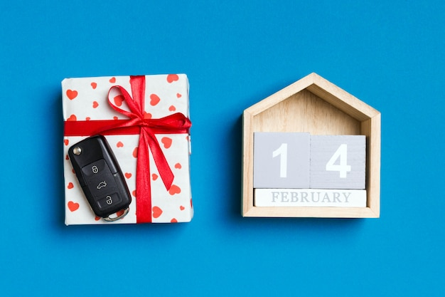 Car key in a gift box with red hearts and festive calendar
