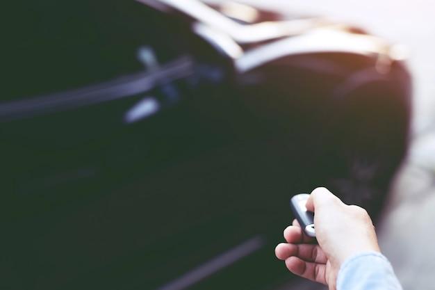 ビジネスマンの手で車のキー。リモートコントロールカーアラームシステムのハンドプレス
