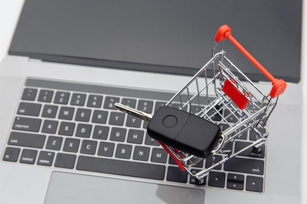 ノートパソコンのショッピングカートの車のキー。オンライン購入車のコンセプト。