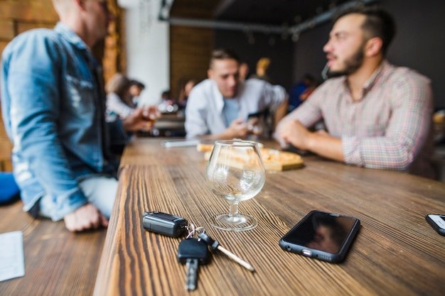 Car key, mobile phone and empty glass on table in the restaurant