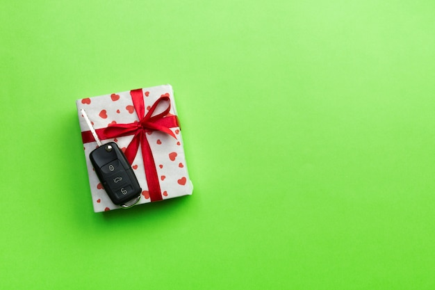 Car key on paper gift box  on green table.