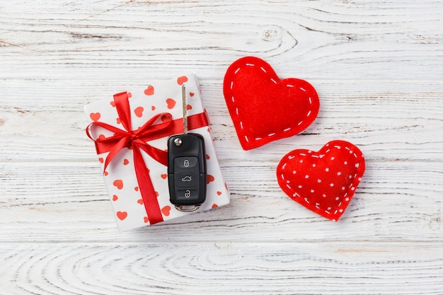 Car key on valentine's day gift box and red hearts