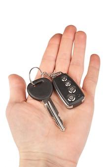 Ключ от машины с будильником в руке, изолированные на белом