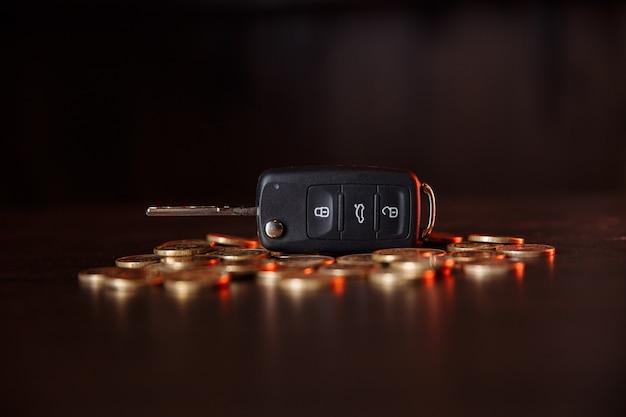 나무 테이블에 동전과 자동차 키입니다. 자동차, 현금에 대 한 무역 자동차에 대 한 돈을 절약의 개념.