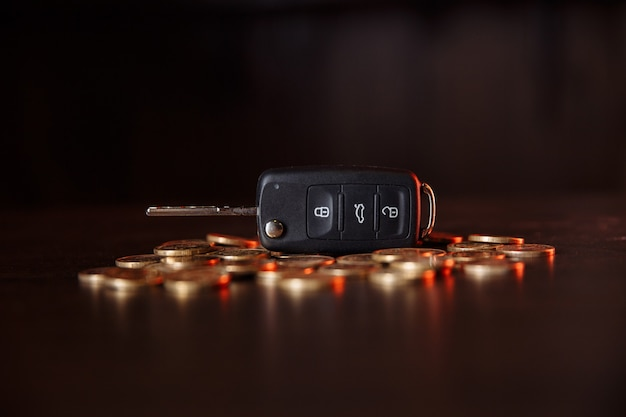 Car key with coins on wooden table. concept of the saving money for car, trade car for cash.