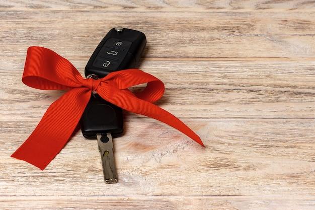 Ключ от машины с красочным бантом на деревянных фоне.