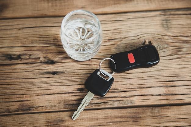 Car key with glass of vodka on desk