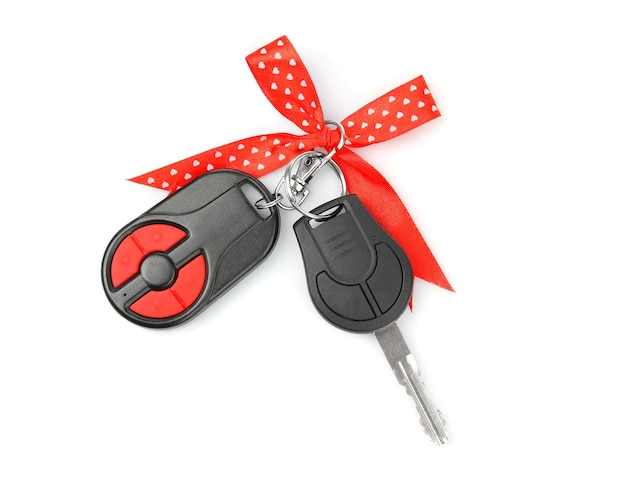 Car key with red bow isolated on white