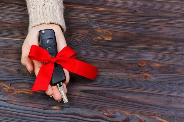 Car key with red bow in woomen hand on wooden background. valentine's day concept