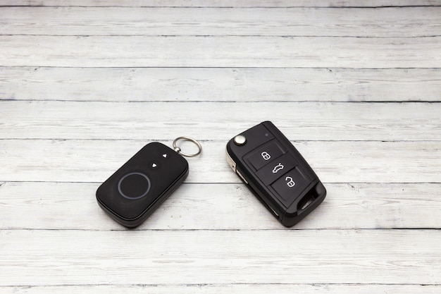 Car key with remote alarm control on the wooden background