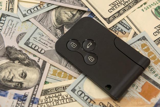 リモコン付きの車のキーと私たちのお金。セール