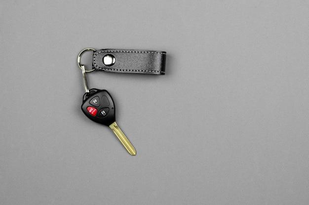 Car key with remote control on grey